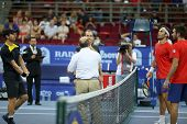 KUALA LUMPUR - SEP 30: The doubles finalists watch as the umpire tosses a coin at the start of the d