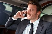 Elegant businessman traveling in luxury car, talking on mobile phone, smiling.