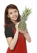 picture of filipina  - Young woman holding a fresh pineapple fruit  - JPG