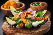 stock photo of chicory  - Delicious field salad with grilled pumpkin stripes for Thanksgiving - JPG