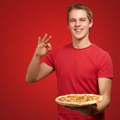 portrait of young man holding pizza and doing good gesture over red background background