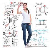 imagens de comprimento total de uma jovem mulher casual, escrevendo os cálculos e gráficos, mantendo seus outros
