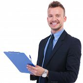 young business man holding a clipboard and a pen and smiling to the camera. on white background