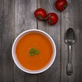 A bowl of tomato soup with a tarnished silver spoon and fresh vine tomatoes, against a rustic wood t