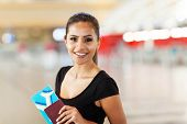 cheerful young business woman with passport and air ticket in airport