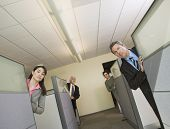 Businesspeople peeking out of office cubicles