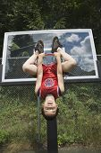 Asian boy hanging upside down on basketball hoop