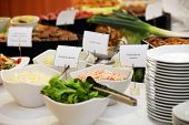 stock photo of buffet catering  - Fresh vegetable salads in dishes on a buffet table with name labels identifying ingredients - JPG