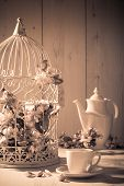 Afternoon tea with birdcage filled with apple blossom in background - vintage tone