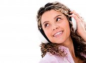 Casual woman with headphones listening to music - isolated over white