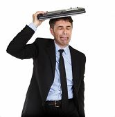 Crying businessman sheltering under his laptop clubbing his heart out in grief, upper body portrait isolated on white