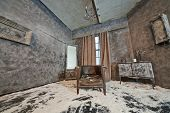 Decoration of abandoned room powdered with snow with old scuffed sagged armchair