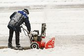 Worker removes snow with hand snowblower