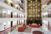 Atrium with red armchairs, couches and elevators in stylish hotel.