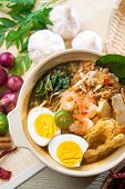 Singaporean prawn noodles or prawn mee. Famous Singapore food spicy fresh cooked har mee in clay pot