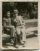 CZESTOCHOWA, POLAND, CIRCA 1934- vintage photo of two men sitting on bench, one of them in uniform, Czestochowa, Poland, circa 1934