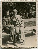 CZESTOCHOWA, POLAND, CIRCA 1934- vintage photo of two men sitting on bench, one of them in uniform, Czestochowa, Poland, circa 1934