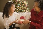 stock photo of granddaughters  - Grandmother giving granddaughter Christmas gift - JPG