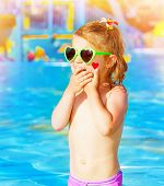 Closeup on sweet baby girl having fun in swimming pool, adorable child with red heart paint print on