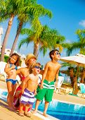 Cute big family standing near poolside and look up in the sky, enjoying summer holiday, facial expre