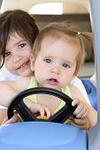 foto of beep  - Two young girls are riding in a toy car - JPG