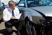 stock photo of wrecking  - Loss Adjuster Inspecting Car Involved In Accident - JPG