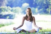yoga woman on green grass in lotus pose