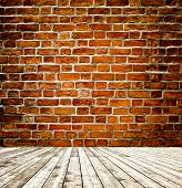 Background of aged grungy textured red brick and stone wall with light wooden floor with whiteboard