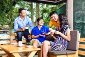 Asian friends or colleagues enjoying leisure time in a cafe, drinking coffee or cappuccino and looki