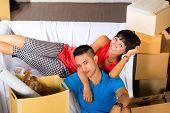 Immobilienmarkt - Paares in der indonesischen Umzug in ein Haus oder eine Wohnung, sie sitzen auf der