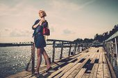 Stylish beautiful blond woman with white scarf and red bag standing near rails of old pier