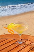 daiquiri cocktail with ice on the table against the background of sea and sky