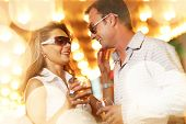 Adult couple enjoying nightlife with glasses of champagne. Shallow DOF.