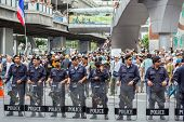 BANGKOK,THAILAND- JUNE 30 : Unidentified polices stand guard on pathumwan road during a Guy Fawkes anti-government rally on Jun 30, 2013 in Bangkok, Thailand.