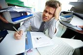 stock photo of fatigue  - Perplexed accountant looking at camera while doing financial reports - JPG