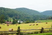 stock photo of split rail fence  - Hay bales and split rail fence are the foreground of this quaint farm in the mountains along the Blue Ridge Parkway - JPG