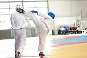 stock photo of shotokan  - Two men practicing martial arts and engaged in a combat one kicking the other - JPG