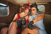 stock photo of gangster necklace  - Pair of pretty 1920s gangster ladies in car - JPG