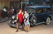 stock photo of tommy-gun  - Group of 1920s gangsters near old car with guns