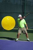 stock photo of pickleball  - Digital image of senior male pickleball player at edge of court hitting a backhand shot - JPG