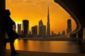 Man watching sunset behind the world's tallest tower Burj Khalifa in Dubai
