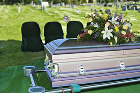 stock photo of funeral  - Image of a steel Casket with Flowers on top in a cemetery - JPG