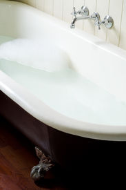 stock photo of hot water  - Old bath tube with bubbles water and hot and cold tap - JPG