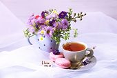 Cup of fresh herbal tea and beautiful bouquet of wildflowers on table