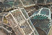 stock photo of lobster boat  - Commercial lobster fishing pots stacked on quayside of a fishing port - JPG