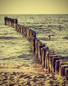 Wood Pilings On Beach, Vintage Retro Effect.