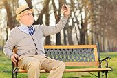 Senior adult taking a selfie in park seated on wooden bench