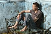 stock photo of felon  - Man on the metal rusty bed in prison - JPG