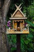 Spirit House In Thailand With Flowers In Vases And Some Wreathes