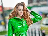 Beautiful woman in bright green coat posing in the rain. Dramatic redhead staying in the rain drops,